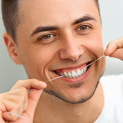 Man with dental implants in Reynoldsburg flossing and smiling